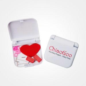 Présentation de la boîte d'accessoires du kit ChiaoGoo Mini Twist, boîte en plastique blanc avec le logo de la marque, ouverte, contenant des grips en forme de coeur rouge, des stoppeurs de câbles rouges, des marqueurs roses et des clés de serrage