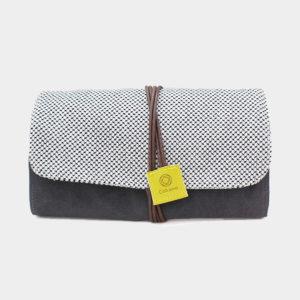 Pochette en tissu Cohana grise et blanche, fermée par un lien en cuir marron avec étiquette jaune