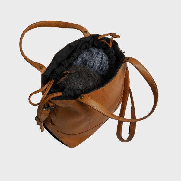 Présentation d'un sac à projet à bandoulière en cuir de la marque Muud, coloris Whisky, ouvert et rempli de laine
