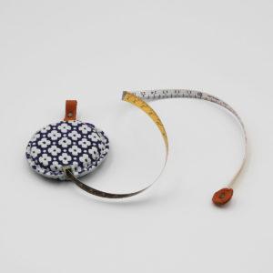Présentation d'un mètre ruban recouvert de cuir bleu à fleurs blanches de la marque Cohana