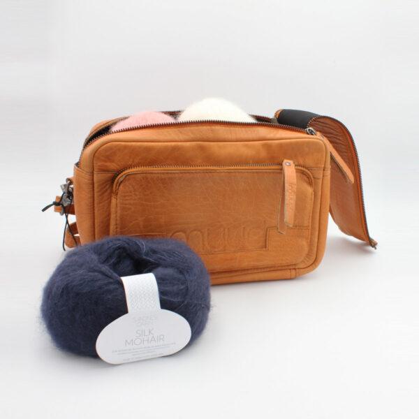 Présentation d'un sac à projet Stavanger de la marque Muud, format trousse à double zip, de couleur whisky, ouvert et rempli de pelotes de laine