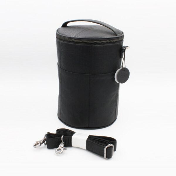Présentation d'un sac à projet Saturn de la marque Muud, en cuir, coloris noir, à côté de sa bandoulière
