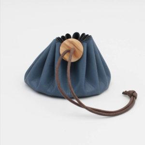 Bourse en cuir bleu fermée par un lien marron et un bouton en bois de la marque Cohana