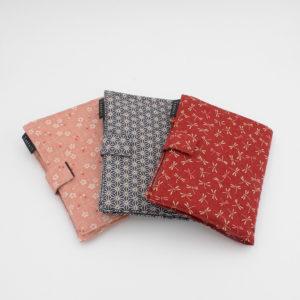 Présentation des trois pochettes en tissu destinées aux kits Seeknit de Kinki Amibari, une rouge à libellules, une bleu marine à imprimé étoiles d'inspiration japonaise et une rose doux à imprimé fleuri sakura