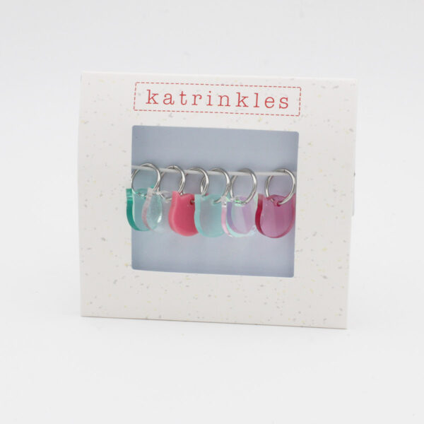 Display of a set of stitch markers made of translucent acrylic and shaped as a cat head, designed by Katrinkles for their Cat Collection