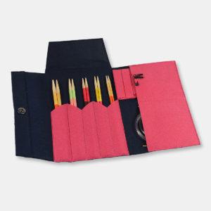 Présentation du kit d'aiguilles circulaires interchangeables Pony Flair, avec pointes en érable coloré, dans une pochette en feutrine rose et bleu marine